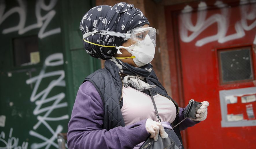 A woman wearing a protective past and googles walks along Canal Street, Monday, April 27, 2020, in the Manhattan borough of New York. (AP Photo/John Minchillo)