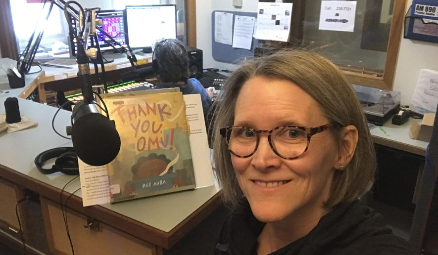 In this April 2, 2020, photo provided by librarian Claudia Haines, she poses for the selfie while preparing to read stories on the air at local radio station KBBI in Homer, Alaska. The library teamed up with the station to continue its popular story hour for preschoolers after it closed to the public amid coronavirus concerns. It's among ways the nation's libraries are dealing with closures amid coronavirus concerns. (Claudia Haines via AP)
