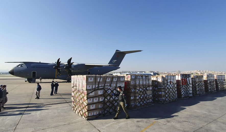 In this handout photo provided by the Turkish Defense Ministry, Turkish soldiers prepare to load a military cargo plane with Personal Protection Equipment donated by Turkey to help United States combat the new coronavirus outbreak, at the Etimesgut airport outside Ankara, Turkey, Tuesday, April 28, 2020. Turkey is sending a planeload of surgical masks, N95 masks and hazmat suits to U.S. to help the country battle the coronavirus outbreak.(Turkish Defence Ministry via AP)