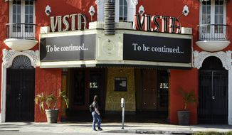 """A pedestrian looks up at a """"To be continued…"""" message on the marquee of the Vista movie theatre, Tuesday, April 21, 2020, in Los Angeles. Movie theaters remain closed as stay-at-home orders continue in California due to the coronavirus pandemic. (AP Photo/Chris Pizzello)"""