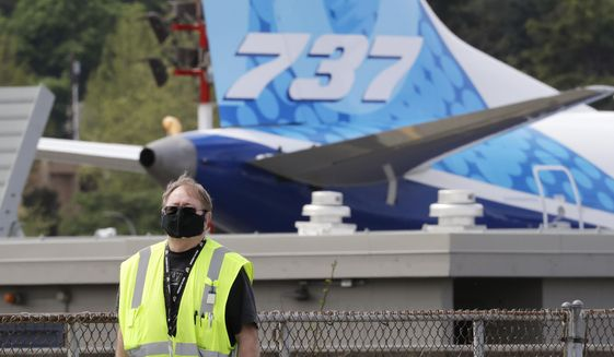 A masked worker walks in view of a 737 jet at a Boeing airplane manufacturing plant Wednesday, April 29, 2020, in Renton, Wash. Boeing says it will cut about 10% of its work force and slow production of planes as it deals with the ongoing grounding of its best-selling plane and the coronavirus pandemic. With air travel falling sharply because of the virus, airlines have delayed orders and deliveries of new planes, reducing Boeing's revenue. (AP Photo/Elaine Thompson)