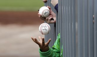 In this March 10, 2020, file photo, a child tosses an already-autographed baseball while awaiting another signature from a passing player before a spring training baseball game between the Los Angeles Angels and the Seattle Mariners in Peoria, Ariz. Doctors, scientists and sports leaders are outlining the path back to playing fields for children in grassroots sports -- an exercise that could inform major organizations on how to get their industries up and running as well in the midst of the COVID-19 pandemic. (AP Photo/Elaine Thompson, File) **FILE**