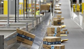 FILE - In this Dec. 17, 2019, file photo, Amazon packages move along a conveyor at an Amazon warehouse facility in Goodyear, Ariz. Amazon will report quarterly earnings on Thursday, APril 30, 2020, providing a first glimpse into its financial performance during the pandemic.  (AP Photo/Ross D. Franklin, File)