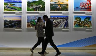 People walk by a display board showcasing China's sweeping infrastructure-building projects at the media center of the Belt and Road Forum in Beijing. African leaders in 2020 are asking what China can do for them as the coronavirus pandemic threatens to destroy economies across a continent where Beijing is both the top trading partner and top lender. (AP Photo/Andy Wong, File)