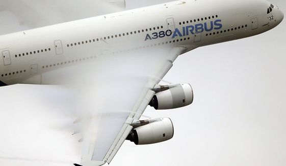 FILE - In this June 18 2015 file photo, vapor forms across the wings of an Airbus A380 as it performs a demonstration flight at the Paris Air Show, Le Bourget airport, north of Paris.  The France-based planemaker Airbus releases quarterly earnings early Wednesday April 29, 2020, at a time of unprecedented upheaval in the aviation industry caused by the spreading the coronavirus and travel lockdowns. (AP Photo/Francois Mori, File)