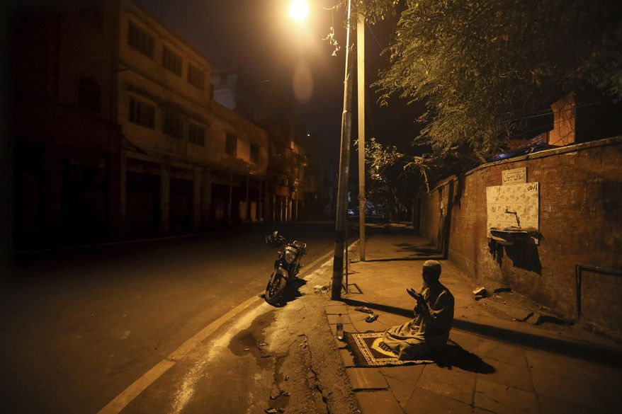 FILE - In this Saturday, April 25, 2020 file photo, a Muslim man prays on a street outside Jama Masjid on the first day of Ramadan during a nationwide lockdown to control the spread of coronavirus, in New Delhi, India. (AP Photo/Manish Swarup)