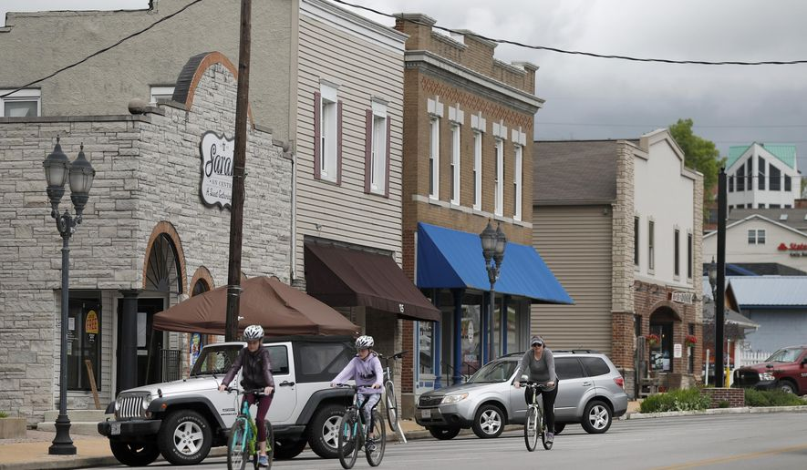 Bicyclists ride past business Wednesday, April 29, 2020, in Eureka, Mo. Eureka Mayor Sean Flower is encouraging business in the town of roughly 10,000 to reopen when the state of Missouri eases restrictions next week put in place to control the spread of the coronavirus despite the fact that St. Louis County, where Eureka is located, has extended its stay-at-home order until at least mid-May. (AP Photo/Jeff Roberson)