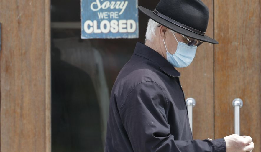 A man walks past a closed business Wednesday, April 29, 2020, in Shaker Heights, Ohio. The U.S. economy shrank at a 4.8% annual rate last quarter as the coronavirus pandemic shut down much of the country and began triggering a recession that will end the longest expansion on record. (AP Photo/Tony Dejak)