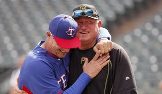 In this May 27, 2016, file photo, Texas Rangers manager Jeff Banister, left, and Pittsburgh Pirates manager Clint Hurdle greet each other during batting practice before a baseball game in Arlington, Texas. Clint Hurdle began sending his daily notes of inspiration more than 10 years ago, during his days managing the Colorado Rockies. They were a simple, small way of checking in with everybody on his staff to discuss leadership ideas or offer support. (AP Photo/Tony Gutierrez, File)  **FILE**