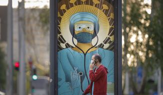 "A man walks by a depiction of a medical staff wearing protective equipment, executed in the style of Christ Pantocrator, in Bucharest, Romania, Wednesday, April 29, 2020. The artwork, among others depicting medical staff in the manner of religious icons, created by designer Wanda Hutira, is part of a campaign called Thank You Doctors, meant to raise awareness to the work of medical staff fighting the COVID-19 pandemic. Following public pressure by Romania's influential Orthodox church the artworks, described as ""blasphemous"", will be removed from all locations in the Romanian capital, according to the agency behind the project.(AP Photo/Vadim Ghirda)"