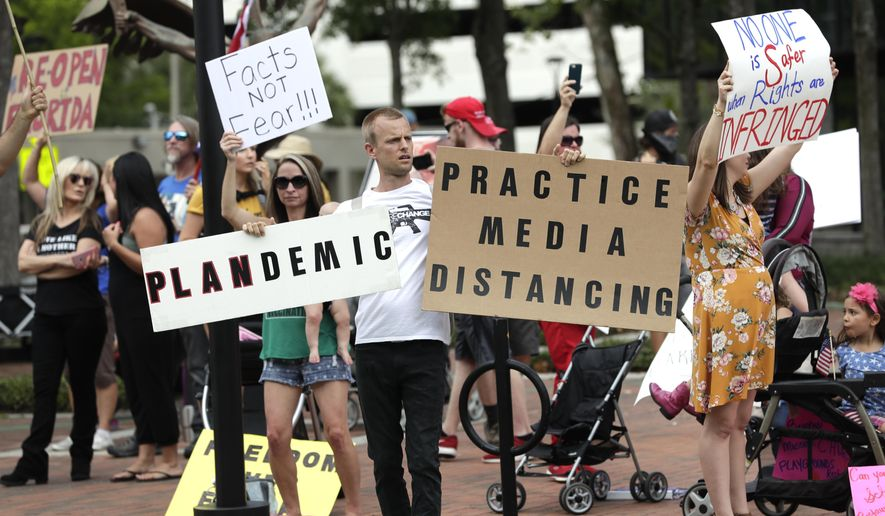 In this April 17, 2020, file photo, protesters demanding Florida businesses and government reopen, march in downtown Orlando, Fla. (AP Photo/John Raoux, File)
