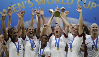 In this July 7, 2019, file photo,  United States' Megan Rapinoe lifts up a trophy after winning the Women's World Cup final soccer match between US and The Netherlands at the Stade de Lyon in Decines, outside Lyon, France. The  global players' association released its report on the state of  women's soccer, after warning that the coronavirus  outbreak could have a disastrous impact following the gains of last summer's Women's World Cup.  (AP Photo/Alessandra Tarantino, File)  **FILE**