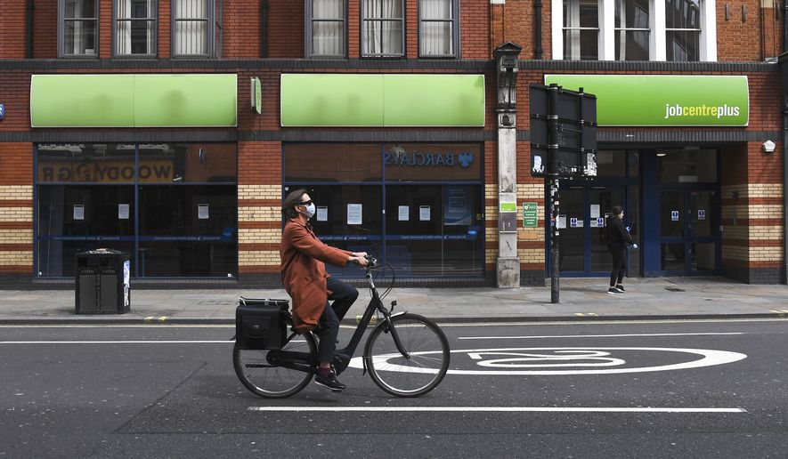 A woman wearing a mask to protect against coronavirus, rides a bicycle past a job centre in Shepherd's Bush, as the lockdown to curb the spread of coronavirus continues, in London, Thursday, April 30, 2020. (AP Photo/Alberto Pezzali)