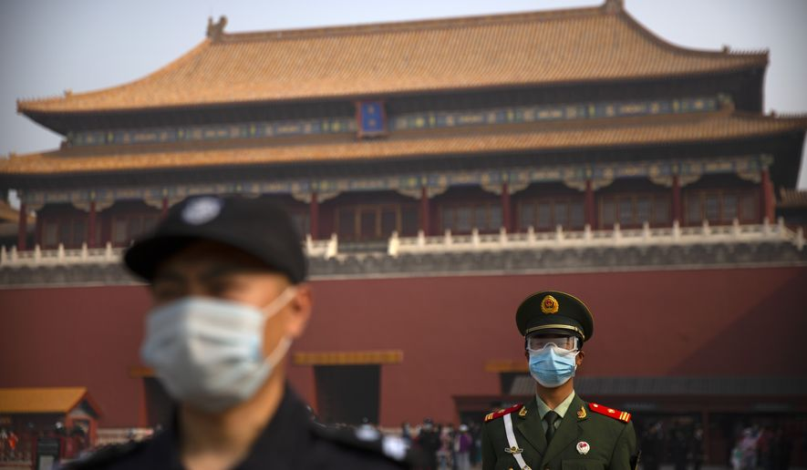 Chinese paramilitary police and security officers wear face masks to protect against the spread of the new coronavirus as they stand guard outside an entrance to the Forbidden City in Beijing, Friday, May 1, 2020. The Forbidden City reopened beginning on Friday, China's May Day holiday, to limited visitors after being closed to the public for more than three months during the coronavirus outbreak. (AP Photo/Mark Schiefelbein)