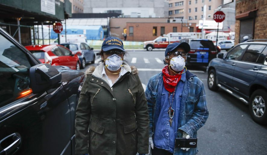 Sandra Perez, left, and Fransisco Ramirez, right, stand outside Elmhurst Hospital Center after delivering a box of donated groceries to a man in need, Saturday, April 18, 2020, in the Queens borough of New York. Some are former construction workers or cleaning ladies who lost their jobs and can barely pay rent, but they go out each day to deliver donated diapers, formula or food to families in need. Through Spanish-speaking chats in Facebook or word of mouth, small groups of immigrants find out who needs the help and they deliver it traveling by car or by foot, exposing themselves to the coronavirus that has already hit hard working-class neighborhoods. (AP Photo/John Minchillo)