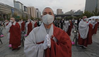 Buddhists monks wearing faces masks to help protect against the spread of the new coronavirus pray to celebrate the Buddha's birthday at the Gwanghwamun Plaza in Seoul, South Korea, Thursday, April 30, 2020. (AP Photo/Ahn Young-joon)