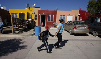 In this Jan. 28, 2020, file photo, Ruth Aracely Monroy, right, rushes her son, Nahum Perla, left, to school from their home on the outskirts of Tijuana, Mexico. They were among the first sent back to Mexico under a Trump administration policy that dramatically reshaped the scene at the U.S.-Mexico border by returning migrants to Mexico to wait out their U.S. asylum process. (AP Photo/Gregory Bull) ** FILE **