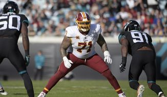 In this Dec. 16, 2018, file photo, Washington Redskins offensive tackle Trent Williams (71) sets up to block in front of Jacksonville Jaguars defensive end Yannick Ngakoue (91) during the second half of an NFL football game in Jacksonville, Fla. After sitting out last season in a dispute in Washington, seven-time Pro Bowl left tackle Trent Williams is excited to start over in San Francisco. (AP Photo/Phelan M. Ebenhack, File)  **FiLE**