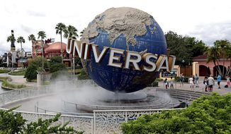 FILE - In this Aug. 5, 2019 file photo, guests cool off under a water mist by the globe at Universal Studios City Walk at Universal Studios Florida in Orlando, Fla. In the wake of the coronavirus crisis, the company that owns Universal theme parks around the world says it's delaying construction on a fourth theme park in Florida and that the opening of a Nintendo-themed park in Japan will be pushed back by a few months.Comcast CEO Brian Roberts said Thursday, April 30, 2020 that the company was delaying construction on its fourth park at Orlando Universal Resort. The Epic Universe theme park was announced last year to great fanfare. (AP Photo/John Raoux, file)