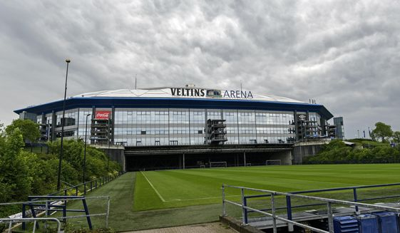 Rain clouds draw over the stadium Veltins Arena and the rolled out pitch of Bundesliga club FC Schalke 04 in Gelsenkirchen, Germany, Wednesday, April 29, 2020. Despite a ban in Germany on all large gatherings through the end of August to fight the coronavirus pandemic, soccer officials are hoping to restart the league without spectators in May. (AP Photo/Martin Meissner)
