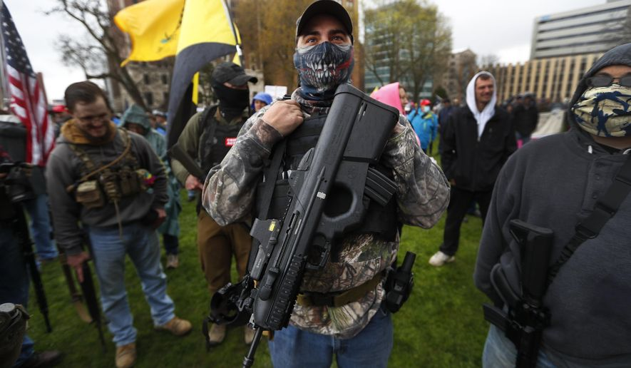 A protester carries his rifle at the State Capitol in Lansing, Mich., Thursday, April 30, 2020. Hoisting American flags and handmade signs, protesters returned to the state Capitol to denounce Gov. Gretchen Whitmer's stay-home order and business restrictions due to the coronavirus pandemic while lawmakers met to consider extending her emergency declaration hours before it expires. (AP Photo/Paul Sancya)