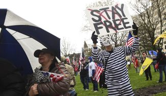 Protesters rally at the state Capitol in Lansing, Mich., Thursday, April 30, 2020. Hoisting American flags and handmade signs, protesters returned to the state Capitol to denounce Gov. Gretchen Whitmer's stay-home order and business restrictions due to COVID-19, while lawmakers met to consider extending her emergency declaration hours before it expires. (Matthew Dae Smith/Lansing State Journal via AP)