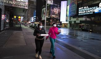 People carry takeout food in New York's Times Square, Wednesday night, April 29, 2020, during the coronavirus pandemic. President Donald Trump said Wednesday the federal government will not be extending its coronavirus social distancing guidelines once they expire Thursday. (AP Photo/Mark Lennihan)