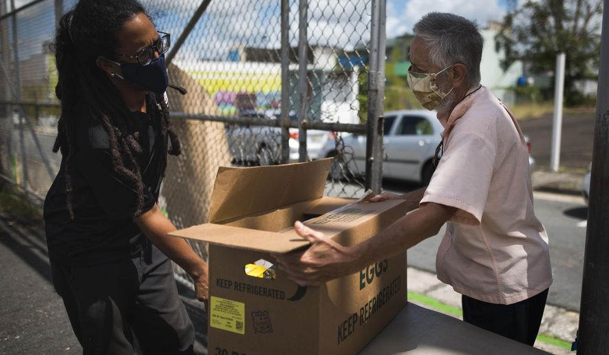 Manuel Berrios, right, takes a food donation from Giovanni Roberto, coordinator of Comedores Sociales (Social Canteens) a non-profit entity dedicated to offering hot meals in the middle of the Covid-19 pandemic, in Caguas, Puerto Rico, Wednesday, April 29, 2020. Puerto Rico's government is refusing to open school cafeterias amid a coronavirus pandemic as a growing number of unemployed parents struggle to feed their children. (AP Photo/Carlos Giusti)