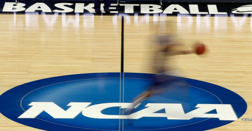 FILE - In this March 14, 2012, file photo, a player runs across the NCAA logo during practice in Pittsburgh. Widespread testing for the new coronavirus will be crucial to having college sports in the fall, especially contact sports such as football and basketball, the NCAA's chief medical officer said, Friday, May 1, 2020. (AP Photo/Keith Srakocic, File)