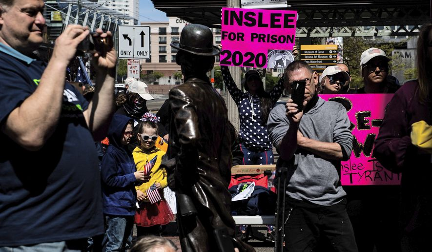 Supporters and media watch as gubernatorial candidate Tim Eyman speaks during a news conference outside of the United States District Courthouse in Union Station in Tacoma, Wash., on Friday, May 1, 2020. Eyman and others sued Gov. Jay Inslee Friday in U.S. District Court in Tacoma, alleging his orders during the pandemic to help stop the spread of COVID-19 have violated their constitutional rights. (Joshua Bessex/The News Tribune via AP)