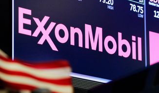 FILE - In this April 23, 2018, file photo, the logo for ExxonMobil appears above a trading post on the floor of the New York Stock Exchange.  Profits fell at Exxon Mobil, Friday, May 1, 2020, during the first quarter as the global pandemic began to erode oil demand. The Irving, Texas oil giant lost $610 million in the first quarter, down 126% from the same time last year.(AP Photo/Richard Drew, File)