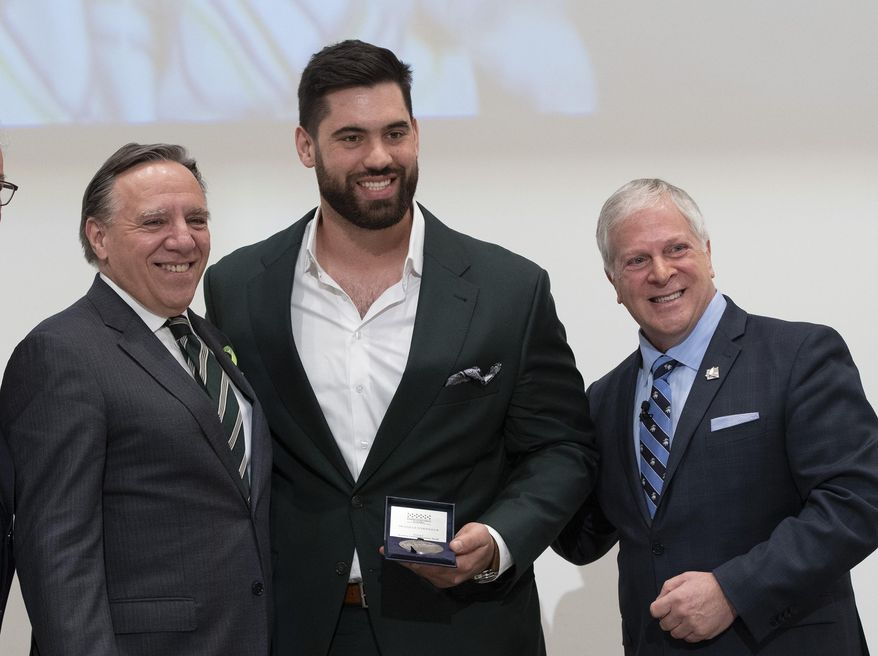 Kansas City Chiefs' Laurent Duvernay-Tardif, center, receives the National Assembly of Quebec Medal of Honour from Speaker Francois Paradis, right, while Quebec Premier Francois Legault, left, looks on, Tuesday, Feb. 18, 2020 at the legislature in Quebec City, Quebec. (Jacques Boissinot/The Canadian Press via AP) ** FILE **