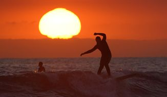 A surfer rides a wave as the sun goes down Thursday, April 30, 2020, in Newport Beach, Calif. The beach is one of the beaches kept open during the coronavirus outbreak. While some communities in Orange County have closed beaches, Huntington Beach and Newport Beach refused to limit access. (AP Photo/Mark J. Terrill)