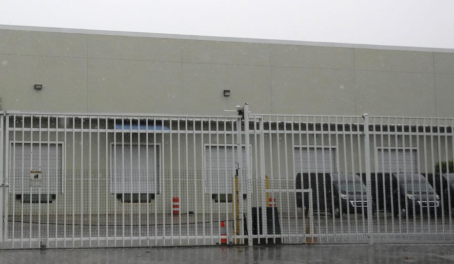 This Thursday, April 30, 2020 photo shows the gate outside a warehouse in Weston, Fla. used by the U.S. Drug Enforcement Agency. A DEA agent and a telecommunications specialist are accused of stealing personal protective equipment, toilet paper and other supplies from the site in Weston, Fla., amid shortages caused by the coronavirus pandemic, law enforcement officials told The Associated Press in March 2020. (AP Photo/Wilfredo Lee)