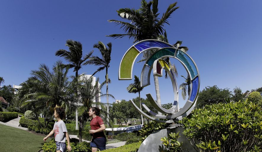 Visitors walk past a stained glass sculpture at the Hollis Gardens, Friday, May 1, 2020, in Lakeland, Fla. The city of Lakeland has reopened some of their city parks with some rules to avoid the spread of the coronavirus. (AP Photo/Chris O'Meara)