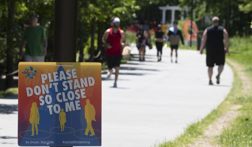 A sign asked people to maintain social distance as they enjoy the warm weather on the Beltline in Atlanta's Inman Park neighborhood Friday, May 1, 2020. Georgia shelter in place order expired Thursday and was not renewed for most Georgians by Gov. Brian Kemp. (AP Photo/John Bazemore)