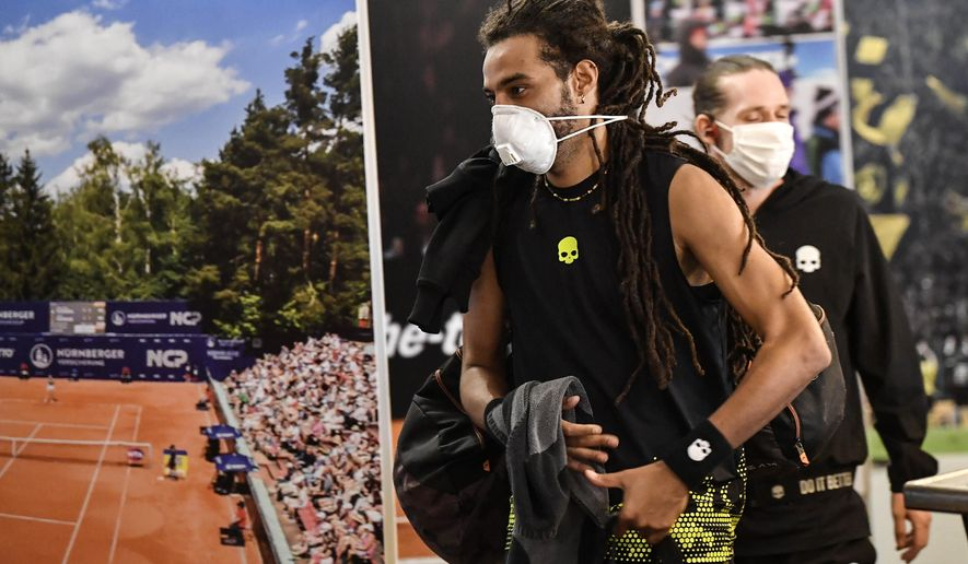Germany's tennis player Dustin Brown wears a face mask as he walks by a poster at a pro-tennis tournament at a local base tennis academy in Hoehr-Grenzhausen, Western Germany, Friday, May 1, 2020. The professional tennis exhibition in the small village in the Westerwald is a rare exception to the global shutdown of sports during the coronavirus pandemic. Matches are played without line judges and without spectators, and broadcasted by remote cameras worldwide. (AP Photo/Martin Meissner)