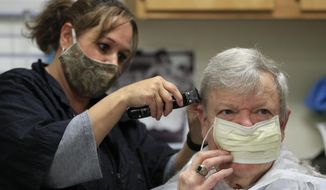 Customer Jan Smith holds his facemask in place while Ann Fouquette trims Smith's hair at Kilroy's Haircutters, Friday, May 1, 2020, in Brunswick, Maine. Gov. Janet Mills has allowed barber shops and some other businesses to reopen Friday under strict guidelines to help prevent the spread of the coronavirus. (AP Photo/Robert F. Bukaty)