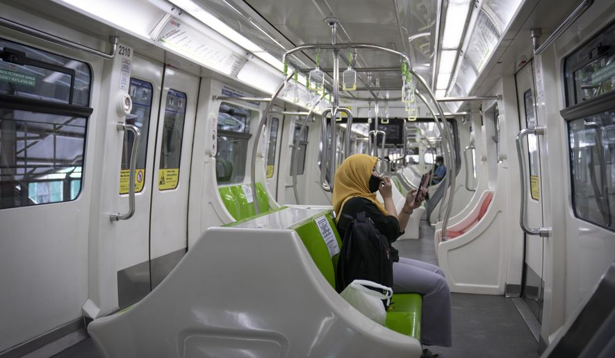 A woman wearing a protective mask uses her phone in a Light Rail Transit train, during the movement control order due to the outbreak of the coronavirus disease COVID-19 in Kuala Lumpur, Malaysia, on Friday, May 1, 2020. Malaysia will allow most business activities to reopen from May 4, Malaysian Prime Minister Muhyiddin Yassin says the economy needs to be revived as billions have been lost during the partial lockdown that began in March. (AP Photo/Vincent Thian)