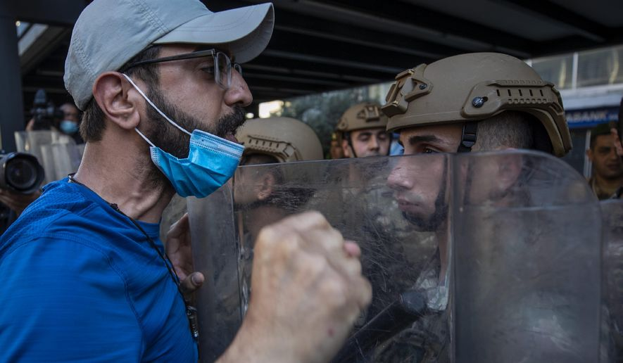 Army soldiers face off with an anti-government protester during May Day protests near the Lebanese Central Bank in Beirut, Lebanon, Friday, May 1, 2020. Hundreds rallied outside the country's central bank and in other parts of the country a day after the prime minister said he'll be seeking a rescue program from the International Monetary Fund to deal with a spiraling economic crisis. (AP Photo/Hassan Ammar)