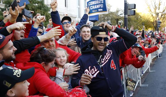 FILE - In this Nov. 2, 2019, file photo, Washington Nationals manager Dave Martinez celebrates with fans during a parade to celebrate the team's World Series baseball championship over the Houston Astros in Washington. Martinez says the World Series champs will raise their banner and present their rings at their stadium with fans in attendance -- no matter how or when or if the 2020 season starts. Like his general manager, Mike Rizzo, Martinez is optimistic there will be a major league season this year and has been mapping out what a second spring training camp might look like. (AP Photo/Patrick Semansky, File)