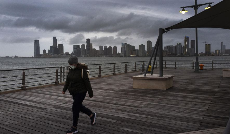 A woman wears a face mask as she walks on Pier 45 in Hudson River Park, Thursday evening, April 30, 2020, in New York. As the new coronavirus pandemic upends lives across the United States, it is taking a widespread toll on people's mental health and stress levels, according to a survey that finds a majority of Americans felt nervous, depressed, lonely or hopeless in the past week. (AP Photo/Mark Lennihan)
