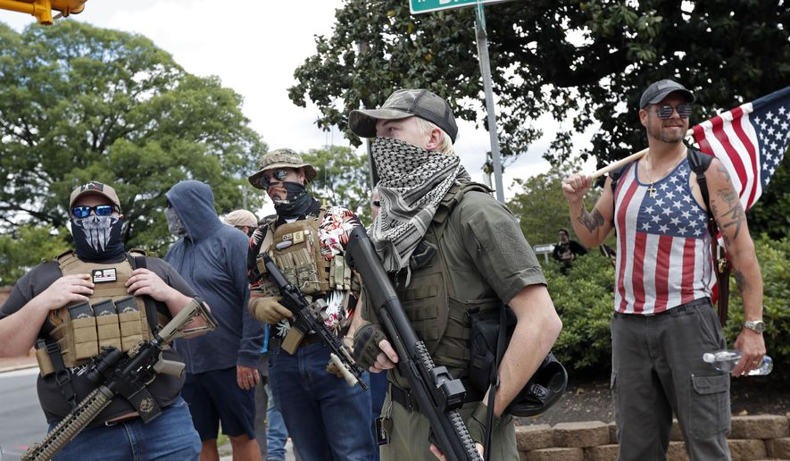 People holding weapons stand on a street corner in Raleigh, N.C., Friday, May 1, 2020. About a dozen demonstrators marched Friday afternoon around the area of the Old Capitol, Legislative Building and Executive Mansion. Several had visible firearms. It was not immediately clear what specific issues they were protesting, as none carried signs. A Facebook post calling for a rally on Friday morning had said it was to promote constitutional free speech and gun rights. (AP Photo/Gerry Broome)