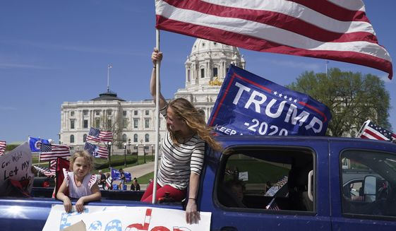 "Supporters of President Donald Trump circle the State Capitol as they protest Gov. Tim Walz's ""Stay Home MN"" orders meant to slow the spread of COVID-19, Saturday, May 2, 2020, in St. Paul, Minn. (Anthony Souffle/Star Tribune via AP) ** FILE **"