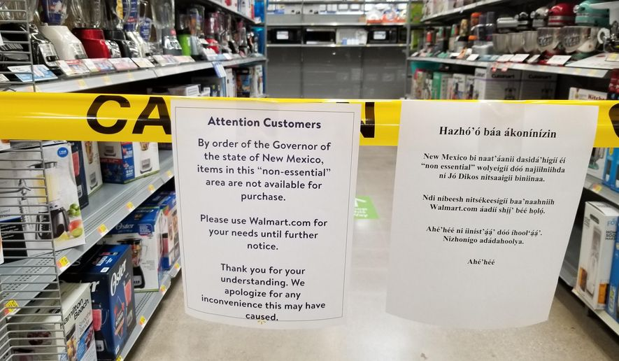 This photo provided by Patrick Sandoval shows signs inside the Walmart in Gallup, N.M., on Friday, May 1, 2020, to advise shoppers that non-essential items aren't available for purchase. (Patrick Sandoval via AP)