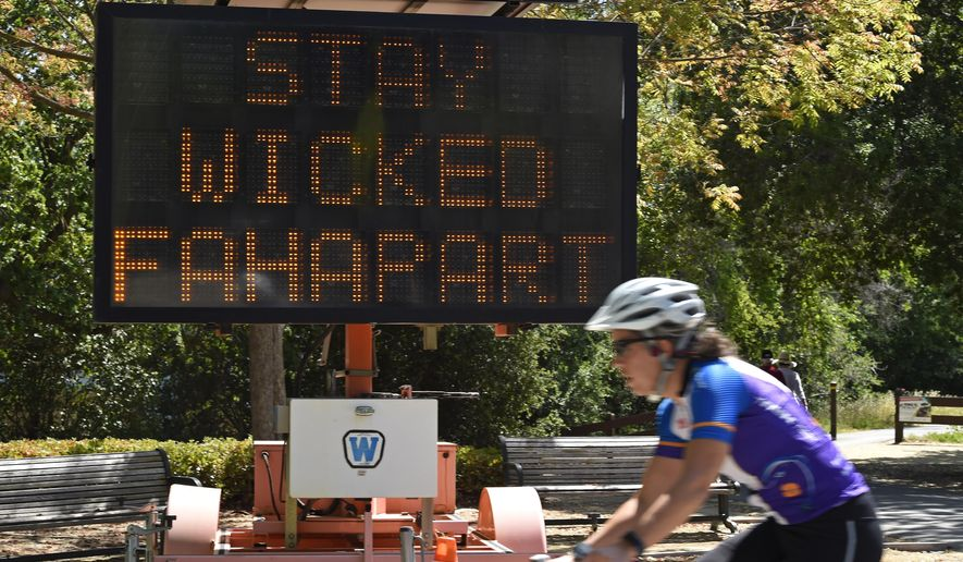 "A bicyclist rides past a road sign that reads ""Stay Wicked Fahapart"" to advise people to maintain distance on the Ironhorse Trail in Danville, Calif., Friday, May 1, 2020, during the coronavirus outbreak. (Jose Carlos Fajardo/Bay Area News Group via AP)"