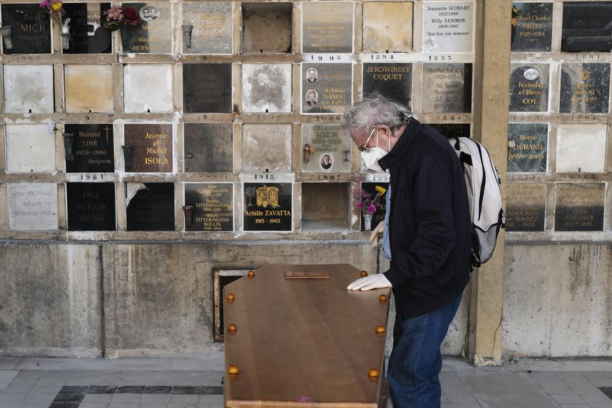 A man pays respect near the coffin of his wife who was 75-years-old, during a funeral ceremony under the care of Paris undertaker Franck Vasseur, at Pere Lachaise cemetery in Paris, Friday, April 24, 2020 as a nationwide confinement continues to counter the COVID-19 virus. (AP Photo/Francois Mori)