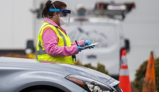In this file photo from April 21, 2020, medical personnel from Montgomery County, Md., check patients arriving for a COVID-19 drive-in testing in Silver Spring, Md.  (AP Photo/Manuel Balce Ceneta) **FILE**