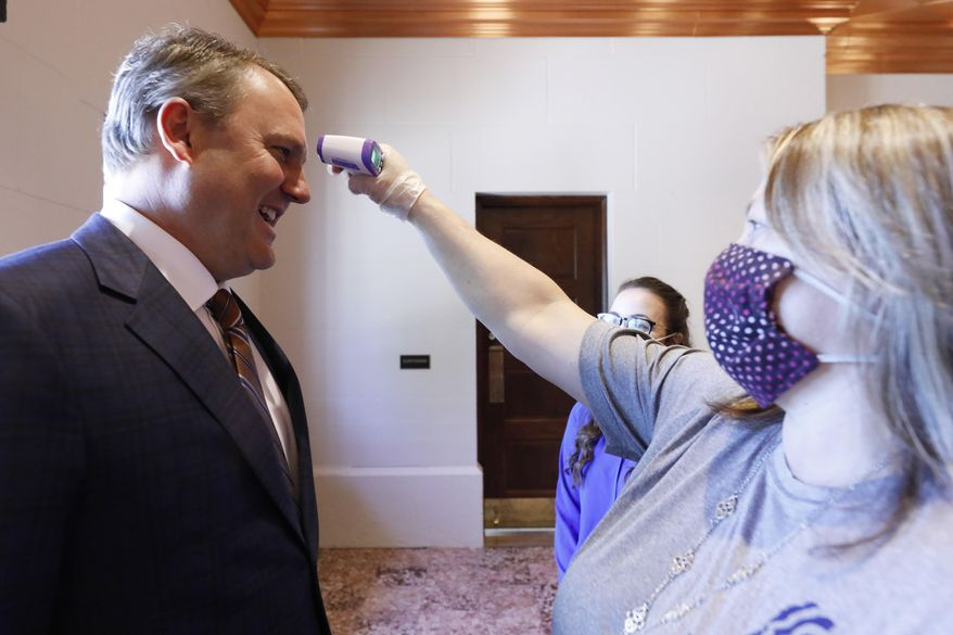 Although he is Speaker Pro Tempore, Rep. Jason White, R-West, has his temperature taken by medical personnel and is asked a series of questions as part of the COVID-19 protocol each person entering the Capitol underwent Friday, May 1, 2020, in Jackson, Miss. (AP Photo/Rogelio V. Solis)