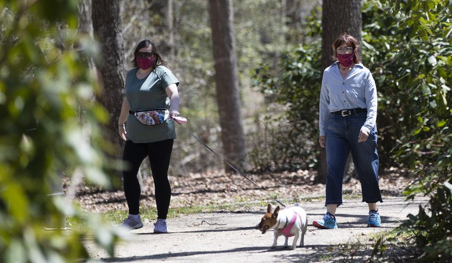 People wearing a protective face coverings hike at Shark River Park in Wall Township, N.J., Saturday, May 2, 2020. Parks and golf courses reopened Saturday after being closed to to the coronavirus pandemic. (AP Photo/Matt Rourke)